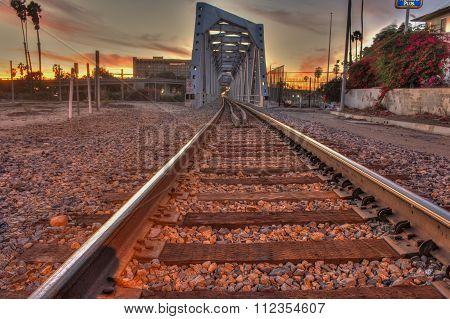 Train tracks headed toward the bridge.
