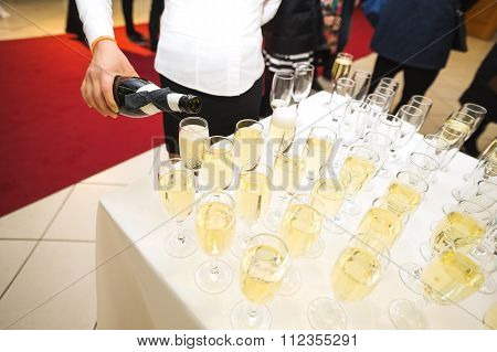Pours champagne in glasses. Big happy holiday