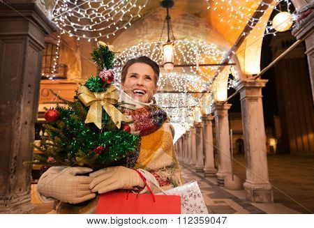 Happy Woman With Christmas Tree And Shopping Bags In Venice