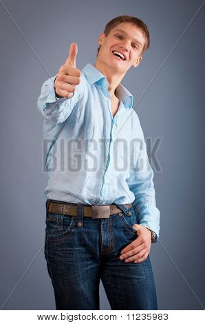 Portrait of a young man showing thumbs up sign