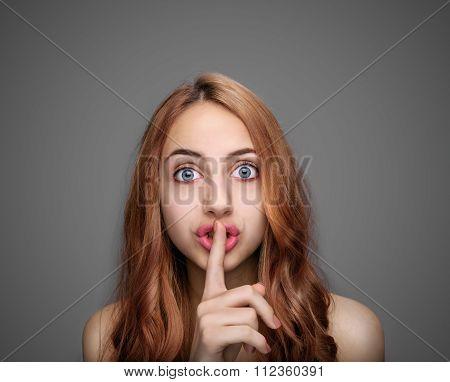 Girl keeping finger on her lips .