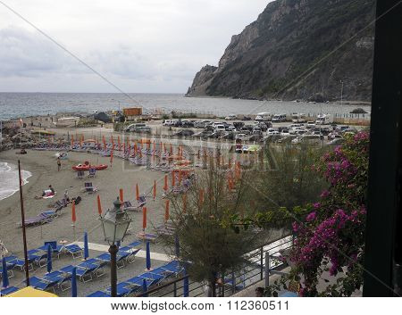 MONTEROSSO ITALY-OCT. 24: The beach with tourists is seen in Monterosso Italy Europe with the cliffs of Cinque Terre in background on the Mediterranean Ligurian Sea on October 24 2015.