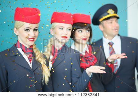 MOSCOW - JUL 09, 2015: A smiling flight attendant with colleagues under the golden rain at DME RUNVAY in Domodedovo