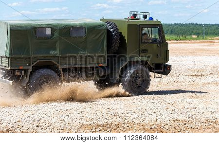 Military vehicle goes on the dusty road