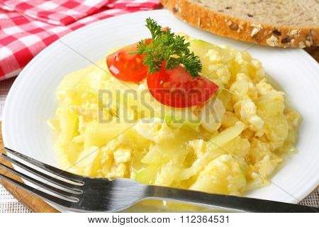 Scrambled eggs with courgette and garlic and slice of whole grain bread