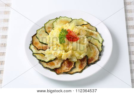 Roasted zucchini slices with potato and egg scramble