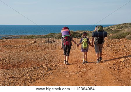 family with large backpacks are on road sea
