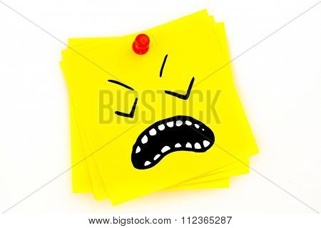 Angry face against sticky note with red pushpin