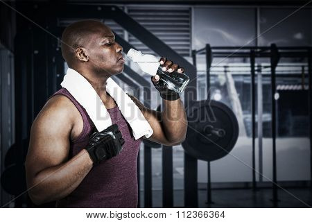 Fit man exercising with barbell against side view of barbells