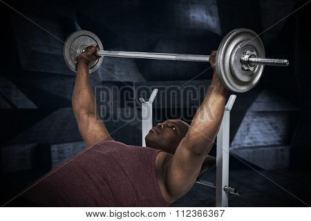 Fit man exercising with barbell against black angular design