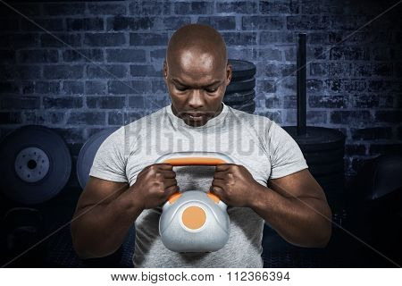 Fit man exercising with kettlebell against kettlebells in front of weights and bossu