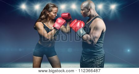 Male and female boxer with fighting stance against desert landscape