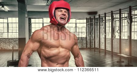 Angry boxer with headgear against gym