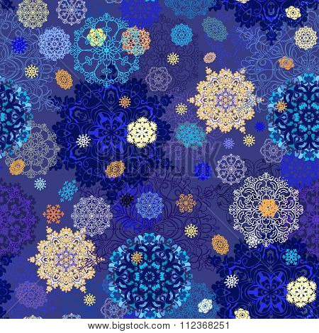 Seamless pattern with golden, blue, white snowflakes and blue background.