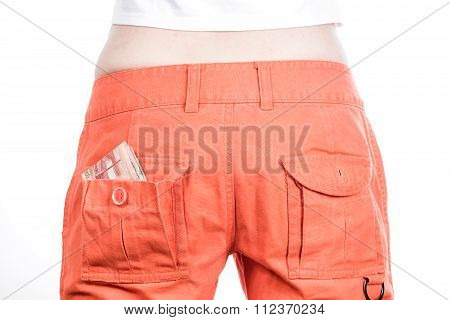 Back view of female buttocks in orange pants with money in pocket.
