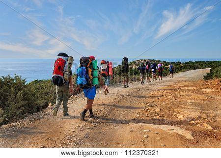 group of tourists with large backpacks are on road sea