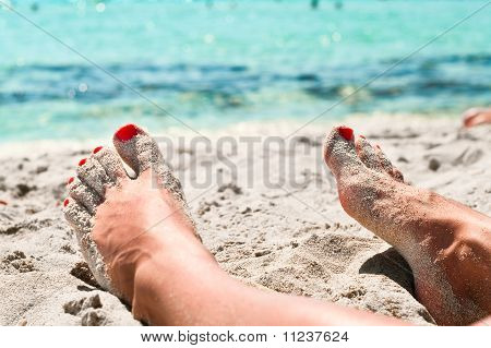 Legs Of Beautiful Young Unrecognizable Girl Lying On A Sand In Beach Near A Sea