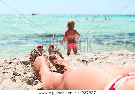 Legs Of Beautiful Young Unrecognizable Girl Lying On Sand In Beach Near A Sea And Little Playing Chi