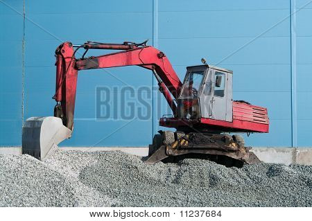 Old Red Excavator With Bucket Beam On Pile Of Crushed Stone