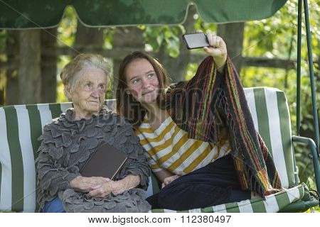 The girl sitting in the hammock with grandma and makes selfie.