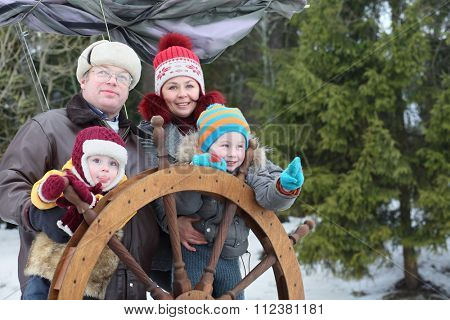 Family of four standing near the wheel of the ship in the winter
