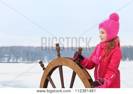 Girl in a pink jacket and hat standing at the helm of the ship in the winter
