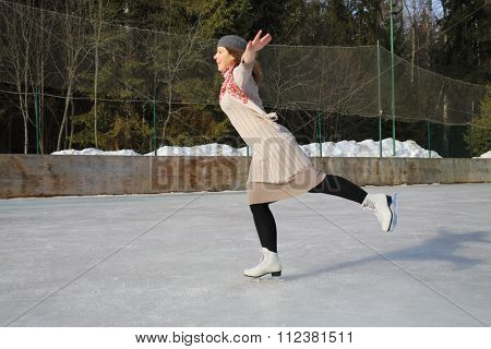 Woman skating on one leg with arms outstretched to the sides on a skating rink