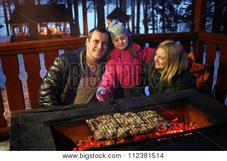 Father, mother and daughter near the brazier with barbecue on a winter evening