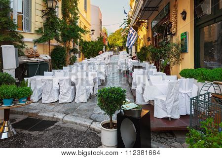 Street of Athens old town with decorated white wedding tables.