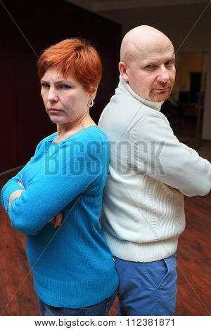 Quarreled wife and husband standing with his hands crossed back to back