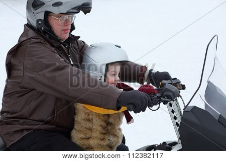 Father with little daughter riding on a snowmobile