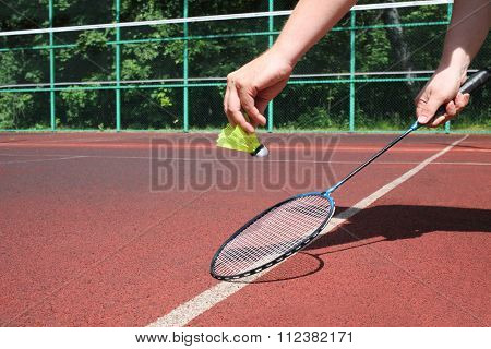 Male hands holding a badminton racket and shuttlecock on the tennis court