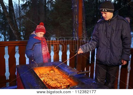 Two boys in jackets and hats doing barbecues on a winter evening