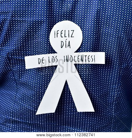 young man with a paper man in his back with the text feliz dia de los inocentes, happy innocents day in spanish, a feast held in spain, hispanic america and philippines equivalent to april fools day
