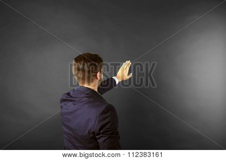 Back view of Caucasian young man in navy blue suit pointing on dark grey background