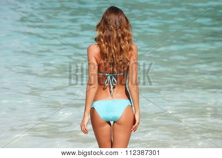Woman in bikini standing on ocean beach on hot summer day