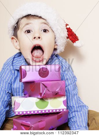 little cute boy with Christmas gifts at home. close up emotional face on boxes in santas red hat. mi