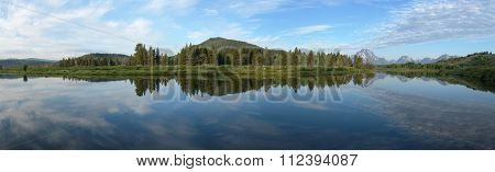 Panoramic view: Snake River reflecting the Rocky Mountains and the sky