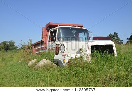 Old truck frame surrounded by grass and boulders