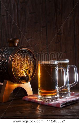 Beer Mugs And Barrel On A Wooden Background