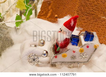 doll of Santa Claus sitting on car in snow
