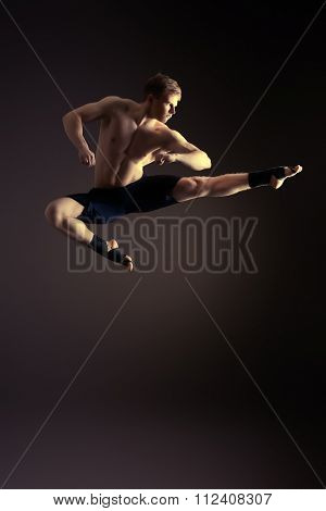 Handsome muscular male athlete doing high jump. Martial arts. Gymnastics.