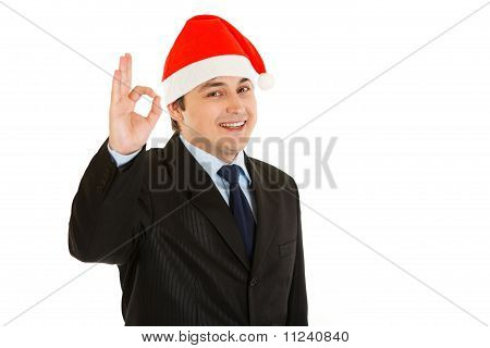 Happy young businessman in Christmas hat showing ok gesture isolated on white.