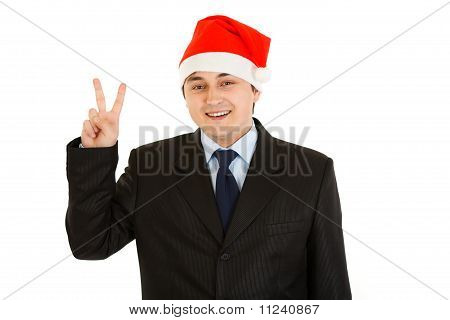 Happy young businessman in Santa hat showing victory gesture isolated on white.