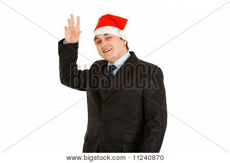 Friendly young businessman in hat of Santa Claus isolated on white. Happy New Year and Merry Christm