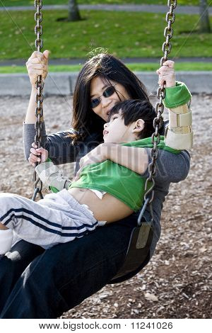 Mother swinging with her disabled son