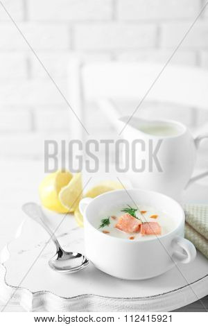 Delicious salmon cream soup on white decorated with lemon and cotton serviette table in the restaurant