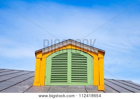 Yellow Wooden Attic Window With Green Shutters