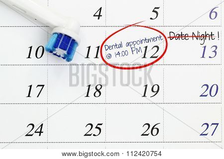Electronic toothbrush head and a dental appointment marked on a white calendar with date night being cancelled.