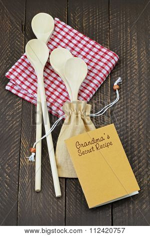 Top view of wooden spoons in beige fabric sack on red gingham tablecloth and a small notebook